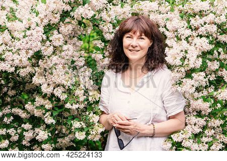 Portrait Nice Woman Of Forty Five Years Old With Brown Hair. Stands Near Large Flowering Bush, Smili