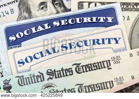 Macro view of Social Security cards, United States Treasury checks and cash.