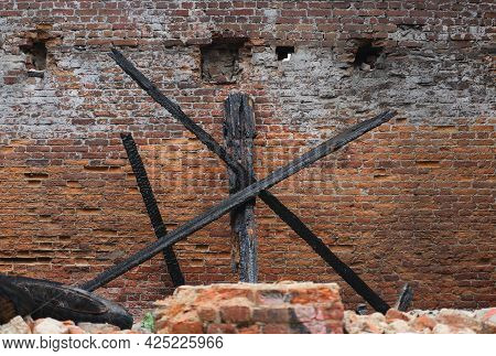 Burnt-out Wooden Beams Against The Brick Wall Of An Old Burnt-out House