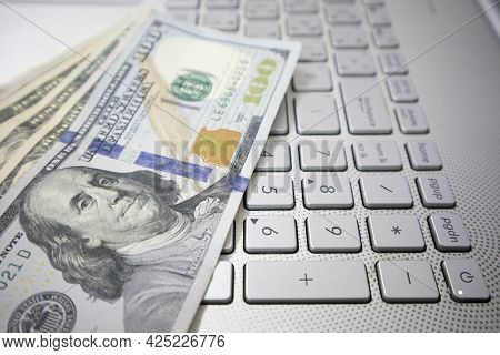 Dollar Bills Are Placed On The Keyboard Of The Laptop. Trading Concept Payments And Investments In T