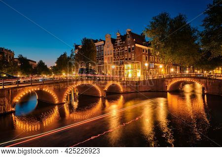 Night view of Amterdam cityscape with canal, bridge and medieval houses in the evening twilight illuminated with blurred boat light trails. Amsterdam, Netherlands