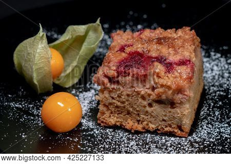 Closeup Shot Of A Freshly Baked Cake With Raspberries, Jostaberries And Rhubarb On A Black Plate Iso