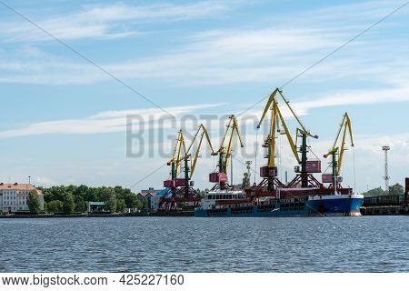 Many Tall Cargo Cranes Stand On The Banks Of The Venta River. Ventspils, Latvia, Baltic Sea.
