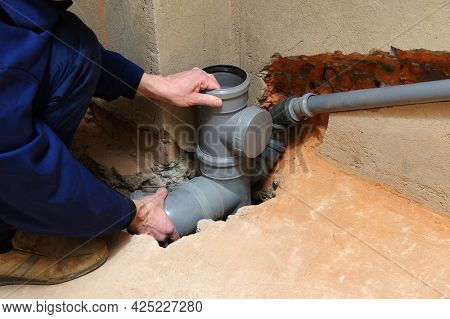Plumber assemble gray pvc sewage pipes. Wastewater drainage system for house.