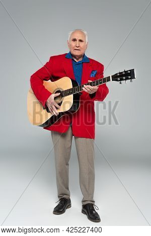 Elderly Man In Red Blazer And Brown Trousers Holding Acoustic Guitar On Grey