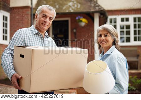 Portrait Of Mature Couple Carrying Boxes On Moving Day In Front Of Dream Home
