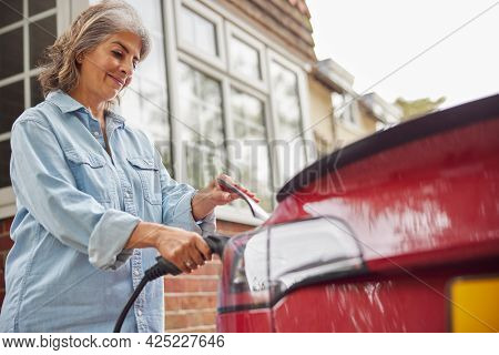 Mature Woman Attaching Charging Cable To Environmentally Friendly Zero Emission Electric Car At Home