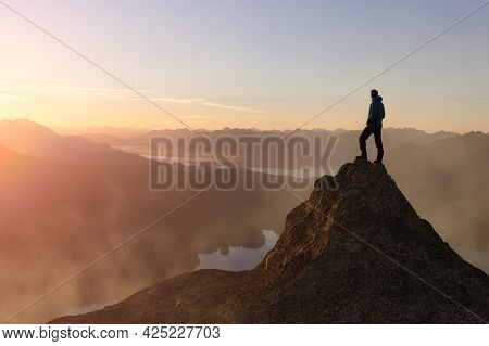 Adventure Composite. Adventurous Adult Man Hiking On Top Of A Mountain. Colorful Sunset Or Sunrise S