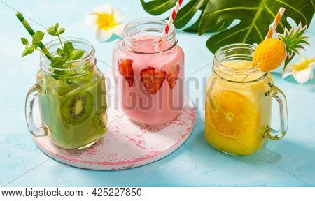 Healthy fresh fruit and berry smoothies in glass jars. Summer cold drinks.