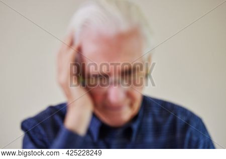 Defocused Concept Shot Of Senior Man Suffering With Mental Health Issues Like Dementia Or Alzheimers