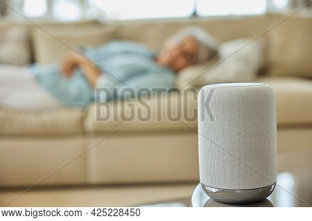 Woman Lying On Sofa Asking Digital Assistant Or Smart Speaker Question