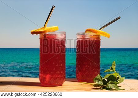 Beach Bar, Summer Sea Resort Concept. Two Drinking Glasses Of Rum Cocktails With Cranberry Juice Dec