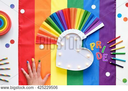 Rainbow Lgbt Flag Background With Frames, Fan, Pencils And Ribbons. Hand With Painted Nails. Lightbo