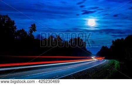 Night Photography With A Long Camera Shutter Speed. Long Lines Of Light From Cars Passing Along The
