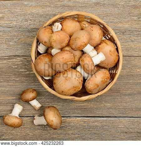 Fresh Champignons In A Basket On A Wooden Table. View From Above.