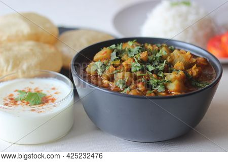 Bottle Gourd Curry With Lentils Served With Steamed Basmati Rice And Deep Fried Whole Wheat Indian F