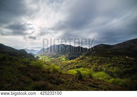 Landscape Of A Green Valley Illuminated By The Sun On A Cloudy Day. Mountains And Nature In Llanes,