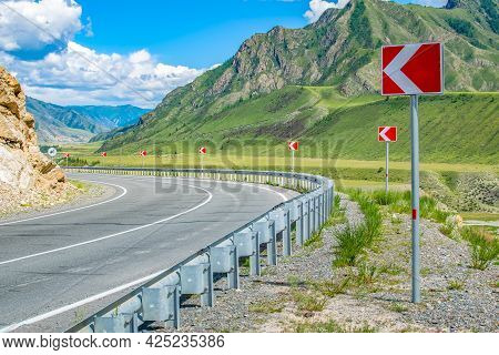A Lot Of Signs, Symbols Warning About A Dangerous And Sharp Turn Of The Road On An Asphalt Highway A