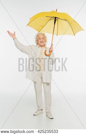 Smiling Elderly Woman In Casual Clothes With Triumph Gesture Standing With Yellow Umbrella On White