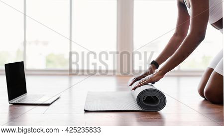 Young Black Woman Unrolling Yoga Mat On Floor Near Pc