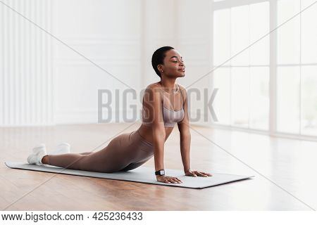 Young Black Woman Stretching Back On Mat, Cobra Pose