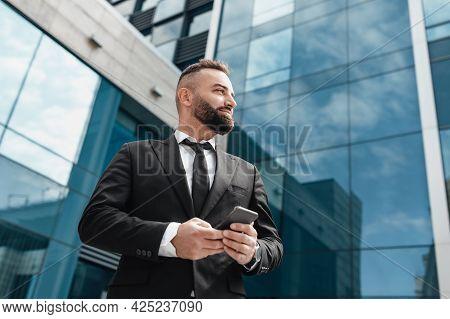 Confident Entrepreneur In Black Suit Holding Smartphone, Standing Against Modern Glass Business Cent