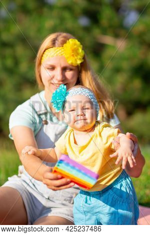 A Young Mother And A Little Daughter In Colored Casual Clothes Are Resting, Sitting On The Lawn And