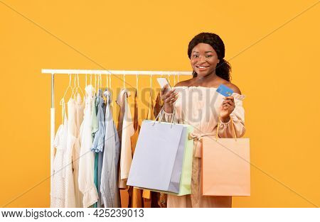 Happy Black Woman Using Smartphone For Online Shopping, Standing Near Clothing Rack With Shopper Bag