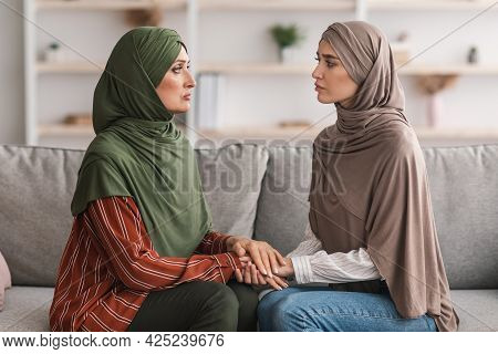 Unhappy Mature Muslim Mother And Adult Daughter Holding Hands Indoor