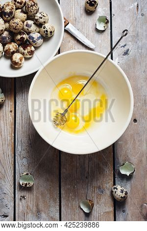 Broken Quail Eggs In A Bowl On A Wooden Background.