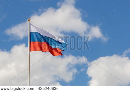 Flag Of The Russian Federation On A Pole Against The Sky With Clouds, Frontal View. The Flag Of Russ