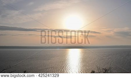 White Sun Shines In High Sky With Light Spindrift Clouds Over Tranquil Water Surface. Sunshine Over