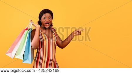 Excited Black Lady In Dress Holding Shopper Bags, Cannot Believe Big Sale, Pointing At Empty Space O