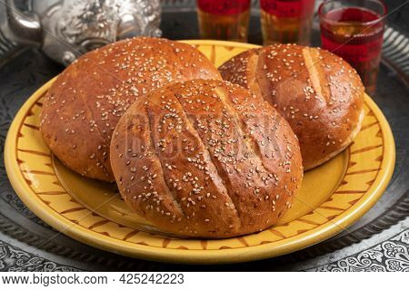 Pair of traditional fresh baked Moroccan krachel, sweet rolls, on a plate close up served with tea