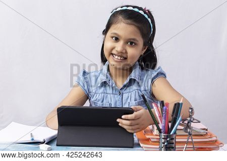 A Pretty Indian Girl Child Looking At Camera While Attending Online Class With Tablet On White Backg
