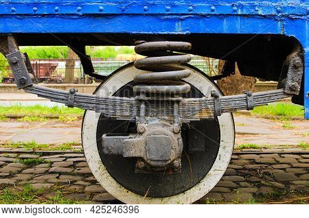 Detailed View Of Metal Wheel Of Old Tram. Steel Wheel Tram. Old Vintage Tram Wheel With Shadows Stay