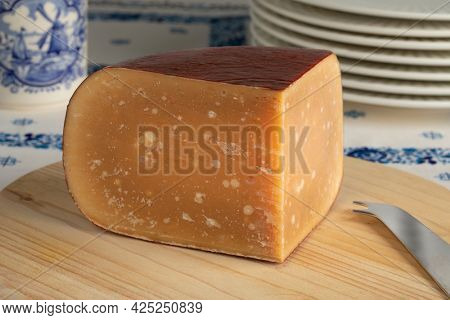 Wedge of old mature Dutch sheep milk cheese on a cutting board
