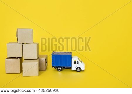 Carton Boxes And Blue Post Truck On Yellow Background. Cargo Transportation, Delivery Service. Trans