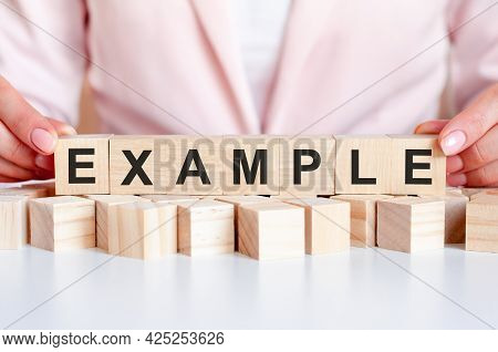 The Hand Puts A Wooden Cube With The Letter Example. The Word Is Written On Wooden Cubes Standing On