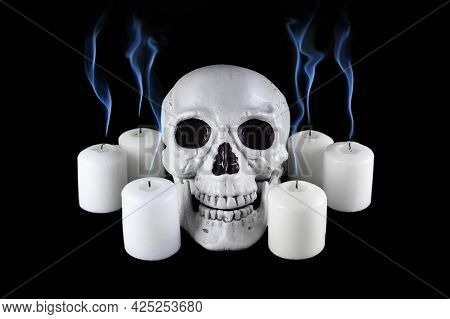 Human Skull Among White Extinguished Candles With Blue Plumes Of Smoke In The Dark, Scary Still Life