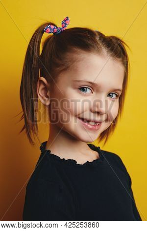 Vertical Close Up Portrait Of Pretty Little Girl Kid With Ponytails Smiling And Wearing Casual Cloth