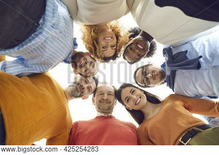 Low Angle Portrait Of Diverse Team Of Happy People Huddling In Corporate Meeting