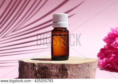 Bottle Of Essential Oil On A Wood Cut With Peony Flowers And Palm Leaf Shadow. Natural Or Alternativ