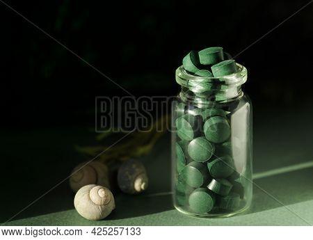 Spirulina Chlorella In Glass Jar, Sea Shells On Green Background. Antioxidant Nutrition. Bio-energy,