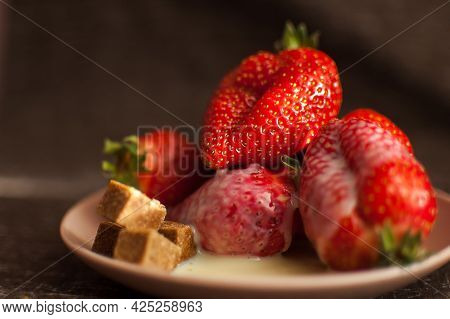Red Ripe Strawberries On Round Plate With A Few Cane Sugar Pieces And Melted White Chocolate