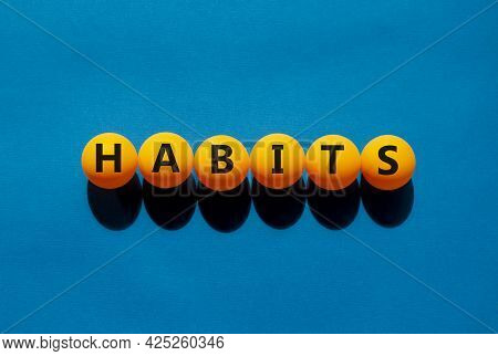 Habits And Business Symbol. The Concept Word 'habits' On Orange Table Tennis Balls On A Beautiful Bl