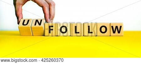 Follow Or Unfollow Symbol. Businessman Turns Wooden Cubes And Changes Words Follow To Unfollow. Beau