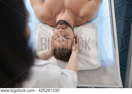 Relaxed Man With Beard Lies On Couch Undergoes Massage Procedure In Clinic