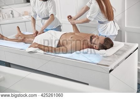 Careful Chiropractics Do Relaxing Massage To Man Patient Lying On Glowing Couch In Clinic