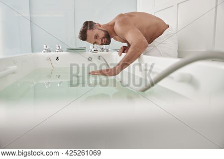 Smiling Man With Bare Chest Touches Clear Water In Modern Hydro Massage Tub In Salon
